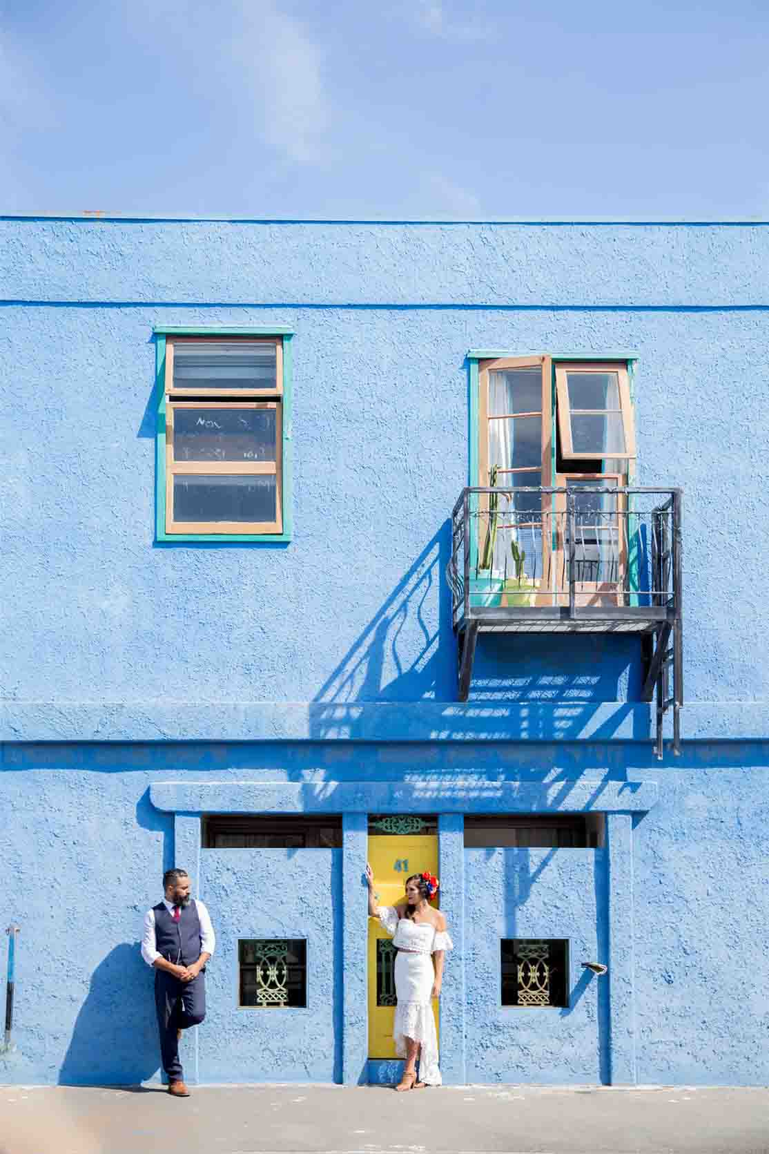 bridal couple posing against a blue wall