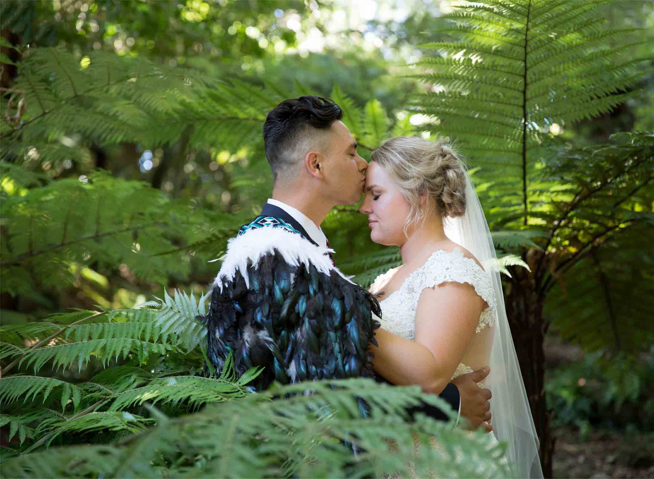 bridal couple standing among ferns