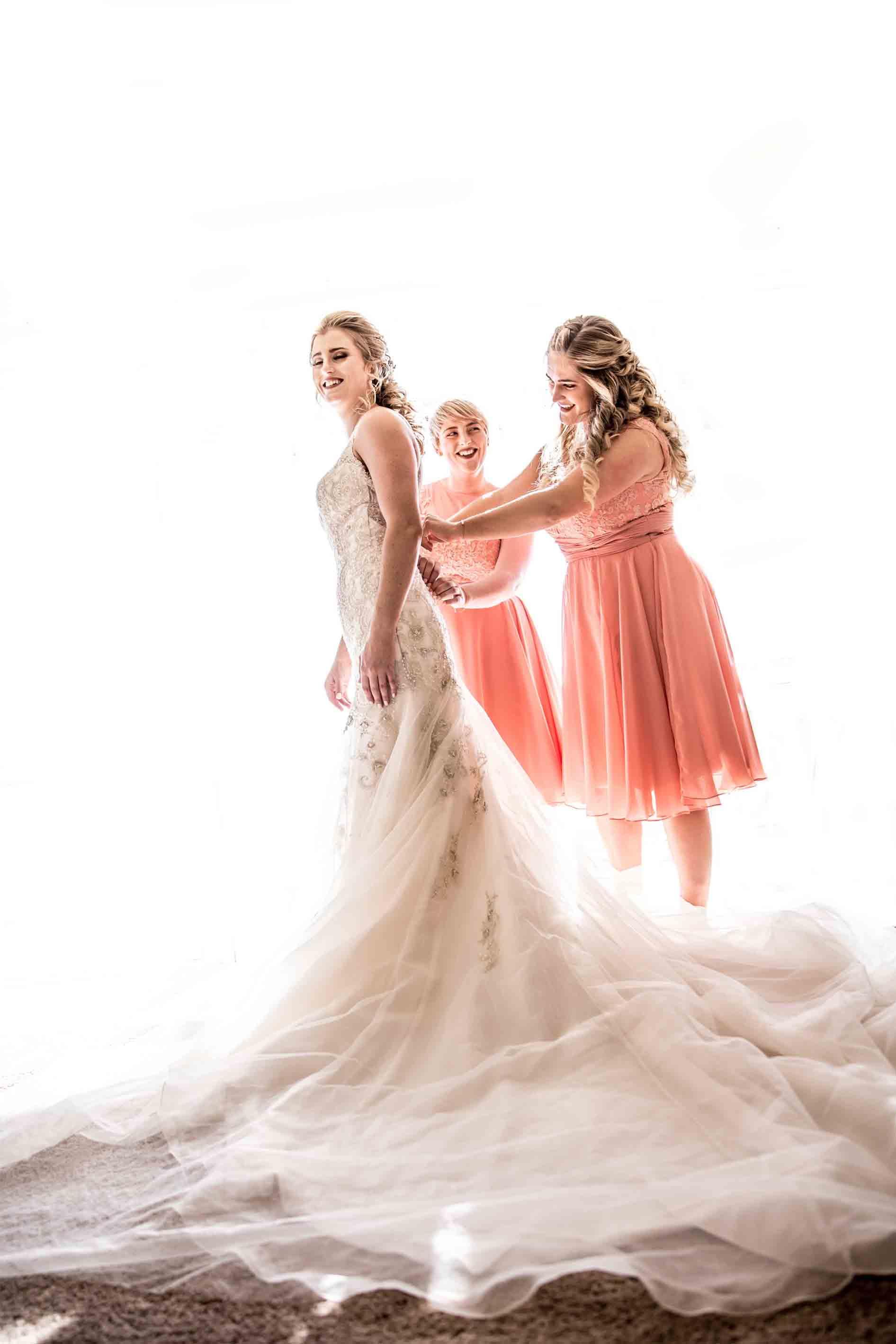 bridesmaids helping bride put on wedding dress