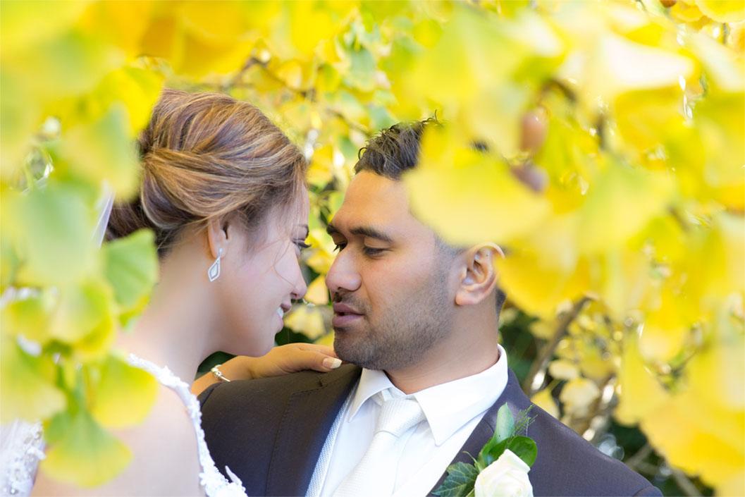 bridal couple posing among autumn leaves