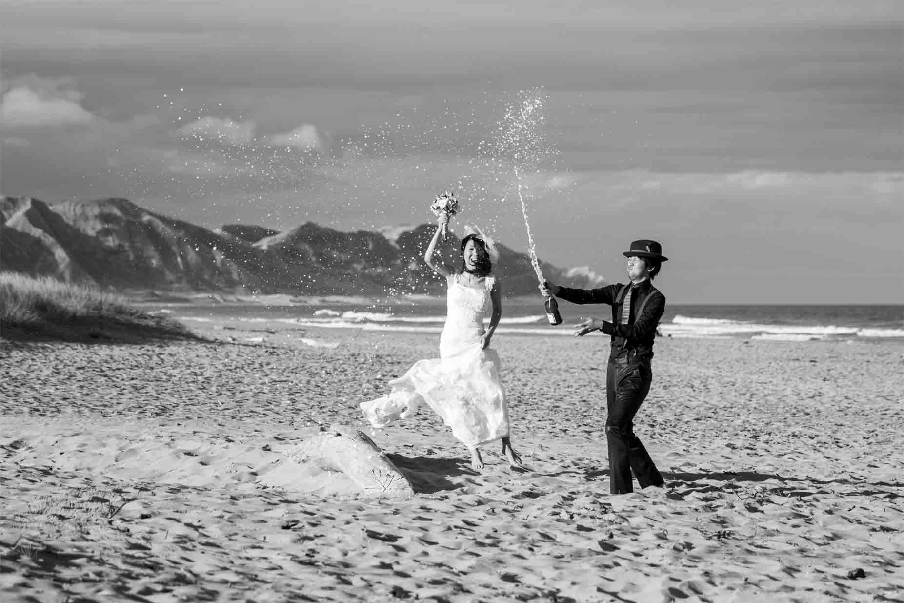 couple popping champaigne cork at the beach